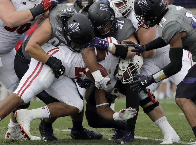 In this Oct. 27, 2018 photo Wisconsin running back Jonathan Taylor is tackled by Northwestern defenders during the first half of an NCAA college football game in Evanston, Ill. Taylor had his worst game of the season for Wisconsin, leaving his race for the national rushing lead with Memphis Darrell Henderson in a virtual dead heat two-thirds of the way through the season. (AP Photo/Nam Y. Huh)