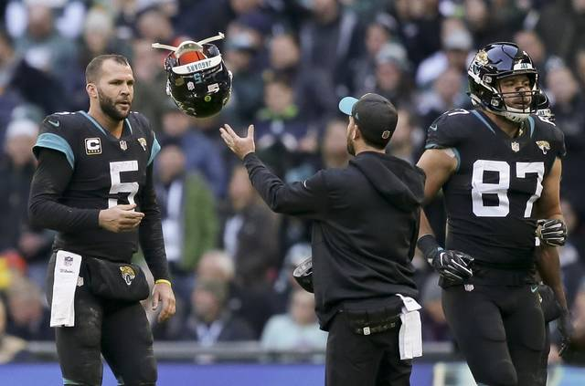 Jacksonville Jaguars quarterback Blake Bortles (5) passes his helmet back after failing in a two point conversion attempt during the second half of an NFL football game at Wembley stadium in London, Sunday, Oct. 28, 2018. (AP Photo/Tim Ireland)