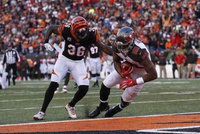 Tampa Bay Buccaneers tight end O.J. Howard (80) scores a touchdown in front of Cincinnati Bengals strong safety Shawn Williams (36) during the second half of an NFL football game in Cincinnati, Sunday, Oct. 28, 2018. (AP Photo/Frank Victores)