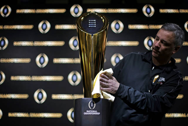 FILE - In this Jan. 7, 2018 file photo Charley Green buffs the NCAA college football championship trophy before a coaches news conference in Atlanta. The College Football Playoff selection committee begins its fifth season Tuesday, Oct. 30, 2018 of presenting weekly rankings and if form holds two schools in the first top four will go on to play in the semifinals. The usefulness of the committee's work and the nationally televised reveal is debatable. But what if anything can be learned from the first four years of CFP rankings? Of the 16 teams the committee ranked in the top four of its initial rankings from 2014-17, half made the playoff. (AP Photo/David Goldman, file)