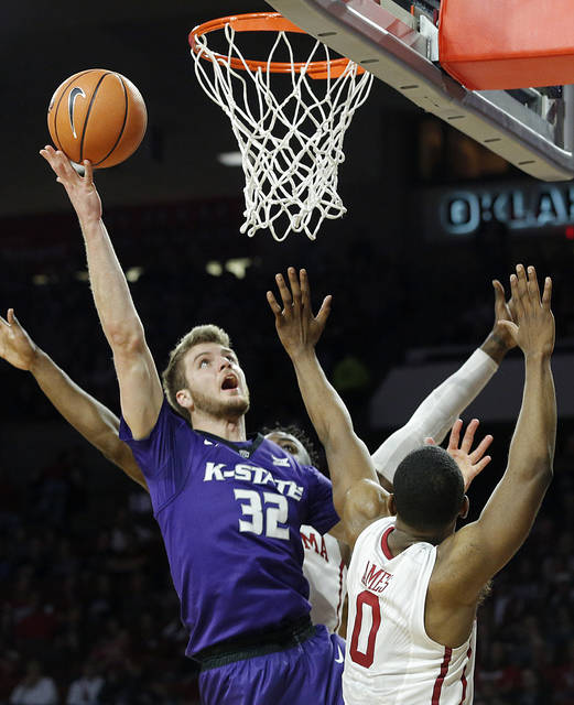 FILE - In this Feb. 24, 2018, file photo, Kansas State's Dean Wade (32) takes a shot against Oklahoma's Christian James (0) and Khadeem Lattin (3) during the first half of an NCAA college basketball game, in Norman, Okla. Big 12 coaches have selected Wade as the conference's preseason player of the year. (AP Photo/Garett Fisbeck, File)