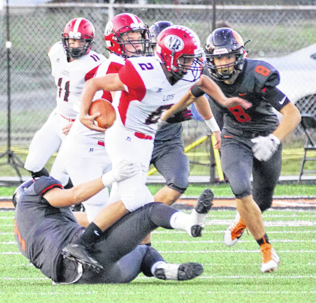 Wilmington's TJ Rockhold (left) has the initial hit on the New Richmond quarterback while teammate Chris Custis moves in for the assist.