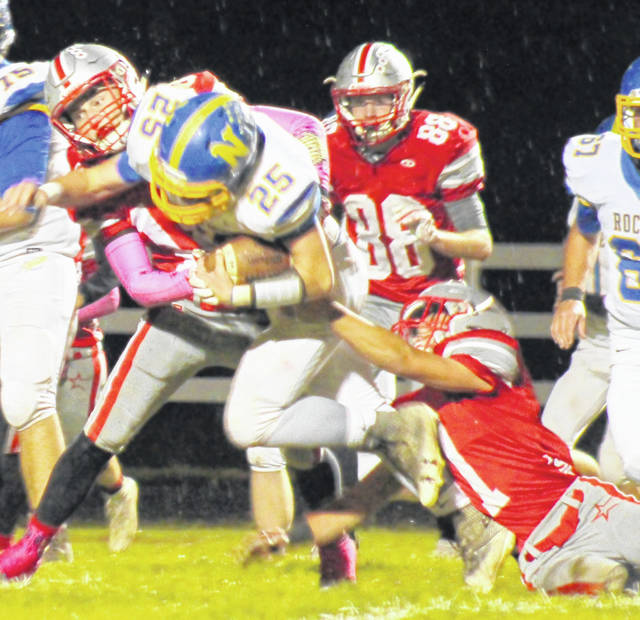 East Clinton's Kaleb Kingery (left) and Austin Rolfe (right) bring down a Clermont Northeastern ball carrier last week.