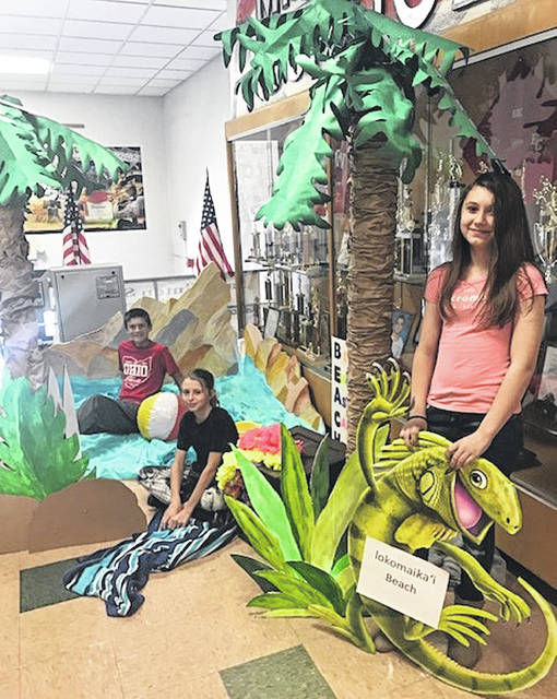 To echo East Clinton Middle School Principal Robbin Luck's line, you could get sand between your toes. There are a number of eye-catching constructed palm trees and other beach-related decorations set up in the building. From background to foreground are students Dakota Collom, Kaitlyn Kratzer and Chloe Jones.