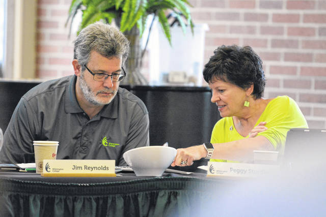 President Jim Reynolds confers with Peggy Sturdivant during the Board of Trustees' summer meeting in July.