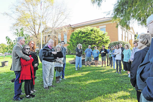 The Wilmington Public Library was the site Saturday morning for the dedication of four trees donated in memory of Tammy McKay, who died in July 2017. The trees are two Nannyberry Viburnums, a Bur Oak and a White Oak. McKay had served as secretary of the former Clinton County Environmental Protection Association, Clinton Streamkeepers, and the Wilmington Tree Commission. Shown, Tammy's husband, Mark McKay, addresses attendees including, from left, grandchild Lexi Burke, son-in-law Cale Burke, daughter Kristin Burke, son-in-law Stuart Maguire (hidden), daughter Tracy Maguire, and grandchild Archer Maguire.