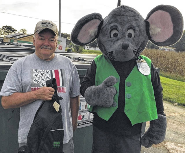"""Jim Carpenter was the first """"culprit"""" in the annual Get Caught Recycling Campaign. Buster the Mouse, from the Clinton County Solid Waste District, caught Jim """"green-handed"""" putting the proper recyclables into the community drop-off recycling container located at Streber's Market in New Vienna. For his efforts in practicing the 3-R's, Jim received several recycled-content prizes, including a backpack, hammock and other items. Don't miss out on this chance to win great prizes by simply recycling household items such as bottles, jars, and newspapers. For a list of the local recycling drop-off locations and acceptable materials, visit the SWMD's website at www.co.clinton.oh.us/recycling. The Get Caught Recycling Campaign will take place all throughout the month of October, so be on the lookout: you could be the next person caught green-handed!"""