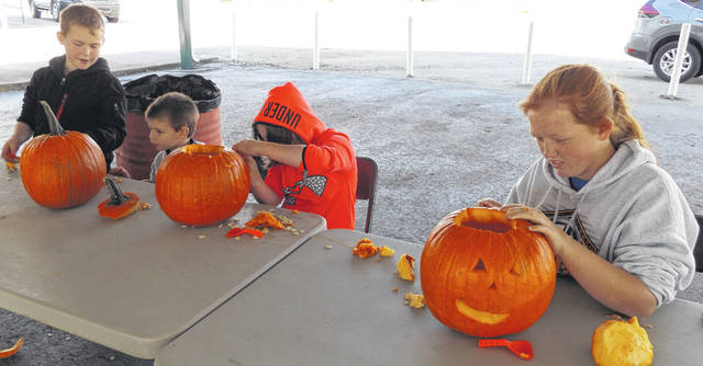 Pumpkins and carving tools were provided children on Saturday at the Fall Camp-Out held at the Clinton County Fairgrounds. From left are Tiegan Rodgers, 9, Brody Woodford, 3, Scarlett Rodgers, 7, and Lacie Sandlin, 14.