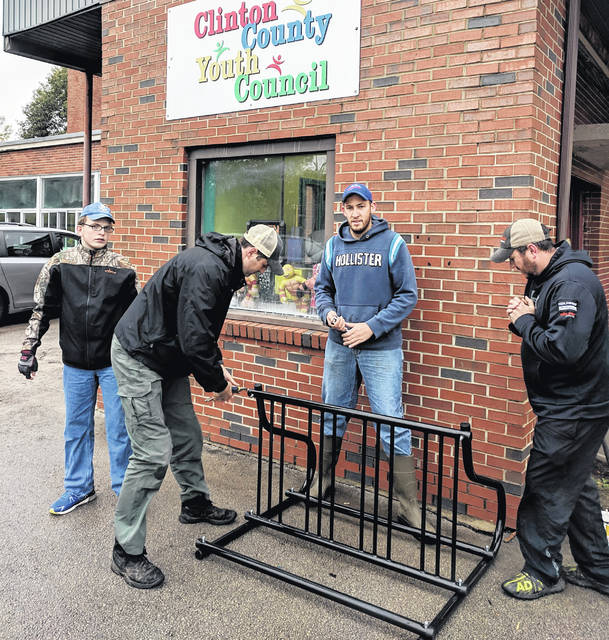 Clarence Bleska, Mat Greene, James Godfrey, and Ryan Bowman work together to assemble the bicycle docking station for Clinton County Homeless Shelter.