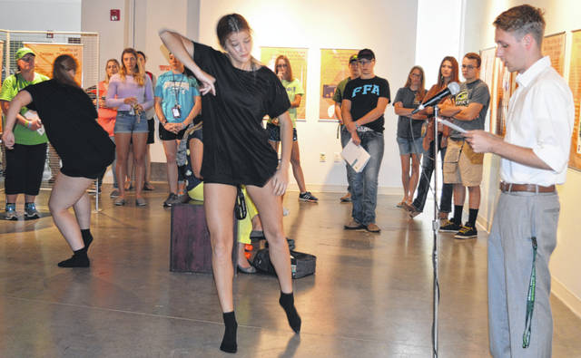 In black outfits, Tara Combs and Emily Potter from All That Dance Studio in Springboro perform movements meant to be chaotic and disturbing, not graceful, in connection with the opioid crisis theme of the peace symposium. They danced during the reading of testimonials.