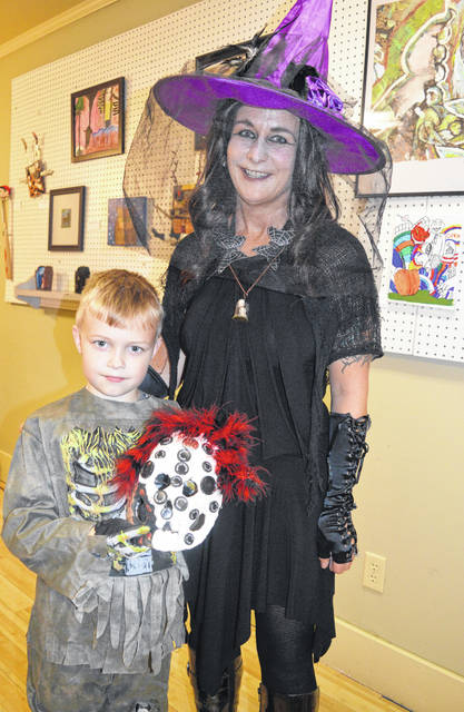 Emory Hollbrook, 7, made a clay and papier-mâché mask for one of his Halloween-themed art projects as a student at Thorngren Studio Arts in downtown Wilmington. For the mask, he also utilized pill bottle caps (a family member works at a pharmacy). Emory used a metal detector at his grandmother's property in search of items to use for re-purposed pieces of art. He stands alongside his art teacher Mary Beth Thorngren during Monday evening's art gallery show with a haunted Halloween theme where costumes were encouraged.