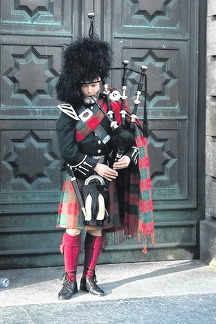 A piper calls the faithful to the kirk, or church, in Edinburgh, Scotland.
