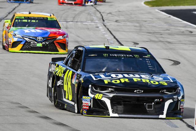 Jimmie Johnson (48) leads Kyle Busch (18) into Turn 1 during a NASCAR Cup auto race at Texas Motor Speedway, Sunday, Nov. 4, 2018, in Fort Worth, Texas. (AP Photo/Larry Papke)