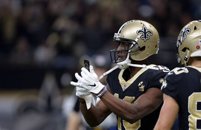 New Orleans Saints wide receiver Michael Thomas (13) pulls out a cell phone after his 72 yard touchdown reception in the second half of an NFL football game against the Los Angeles Rams in New Orleans, Sunday, Nov. 4, 2018. (AP Photo/Bill Feig)