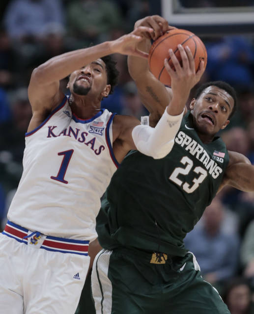 Kansas forward Dedric Lawson (1) fights for a rebound with Michigan State forward Xavier Tillman (23) during the first half of an NCAA college basketball game at the Champions Classic in Indianapolis on Tuesday, Nov. 6, 2018. (AP Photo/AJ Mast)