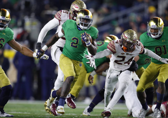 FILE - In this Saturday, Nov. 10, 2018 file photo, Notre Dame running back Dexter Williams (2) runs for a touchdown against Florida State in the second half of an NCAA college football game in South Bend, Ind. Senior Dexter Williams has been through countless ups and downs during his four years at Notre Dame. Injury, suspension, an arrest, the emotions of helping his ailing mother all of it has weighed down Williams at times. He has emerged just the same as the workhorse running back for the third-ranked Fighting Irish, and a key reason Notre Dame has legitimate hopes of making the playoff.(AP Photo/Paul Sancya, File)
