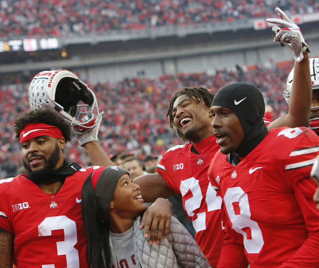 Ohio State's Damon Arnette, left to right, Shaun Wade, and Kendall Sheffield celebrate with fans after beating Michigan in an NCAA college football game Saturday, Nov. 24, 2018, in Columbus, Ohio. Ohio State beat Michigan 62-39. (AP Photo/Jay LaPrete)