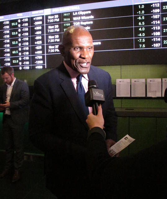 In this Nov. 20, 2018, photo, former New York Giants linebacker Harry Carson discusses a sports bet he had just placed on the New York Yankees to win the 2019 World Series at Resorts Casino in Atlantic City, N.J. Numerous U.S. states are considering joining the seven states that currently offer legal sports betting. (AP Photo/Wayne Parry)