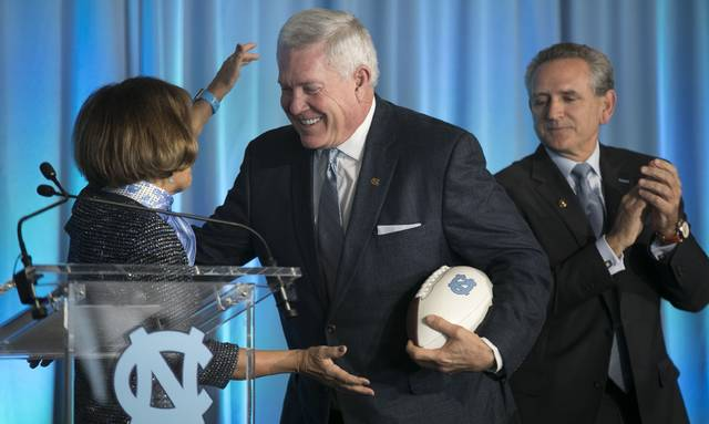 Mack Brown, center, is introduced by University of North Carolina Chancellor Carol Folt, left, as the school's new NCAA college football coach during a news conference, Tuesday, Nov. 27, 2018, at Kenan Stadium in Chapel Hill, N.C. Brown spent 10 seasons at UNC from 1988-97 before leaving for Texas. He left there in 2013 and has been in broadcasting in the years since. (Robert Willett/The News & Observer via AP)