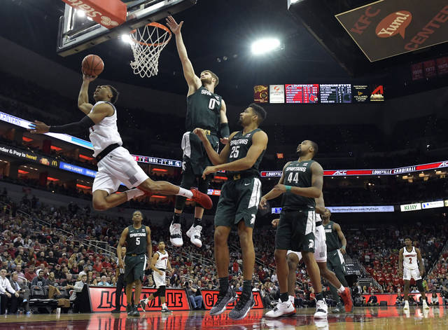 Louisville forward Dwayne Sutton (24) attempts a layup around the defense of Michigan State forward Kyle Ahrens (0) during the second half of an NCAA college basketball game, in Louisville, Ky., Tuesday, Nov. 27, 2018. Louisville won 82-78. (AP Photo/Timothy D. Easley)