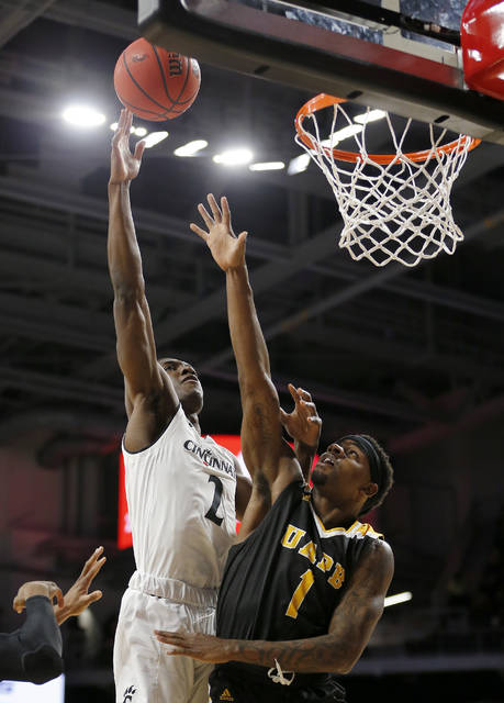 Cincinnati guard Keith Williams (2) puts up a shot over Arkansas-Pine Bluff guard Charles Jackson (1) in the first half of an NCAA college basketball game, Tuesday, Nov. 27, 2018, in Cincinnati. (Sam Greene/The Cincinnati Enquirer via AP)