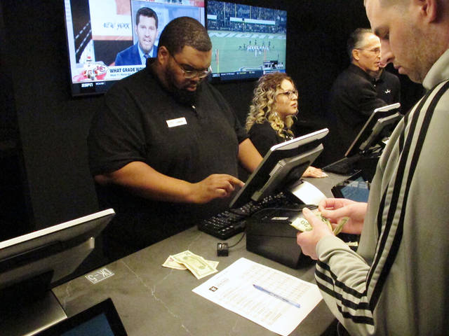 In this Nov. 20, 2018, photo a customer makes a sports bet at Resorts Casino in Atlantic City, N.J. Professional sports leagues that once vehemently fought sports betting are now partnering with gambling companies to get in on it now that it's legal. (AP Photo/Wayne Parry)