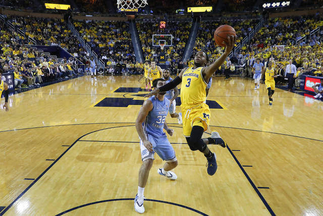 Michigan guard Zavier Simpson (3) drives on North Carolina forward Luke Maye (32) in the first half of an NCAA college basketball game in Ann Arbor, Mich., Wednesday, Nov. 28, 2018. (AP Photo/Paul Sancya)