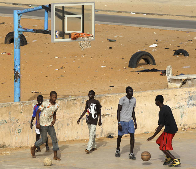FILE - In this Aug. 7, 2010 file photo, soccer and basketball games overlap as boys share space on a basketball court local residents say was built several years ago by Charlotte Bobcats' Dasagana Diop in the neighborhood where he grew up in Dakar, Senegal. The NBA has big plans for Africa where an office was established eight years ago in South Africa and there's an annual exhibition game featuring NBA stars. (AP Photo/Rebecca Blackwell, file)