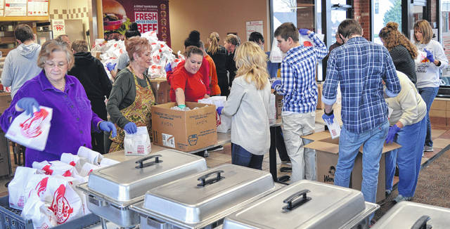 It takes a small army of local residents volunteering their time, money and vehicles to cook, serve and deliver the annual Thanksgiving meals. Shown are just a few of those volunteers at last year's event at Wendy's on Rombach Avenue in Wilmington.