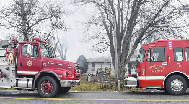 Wilmington and Clinton-Warren firefighters aid in extinguishing a fire on Clarksville Road in Warren County on Friday.