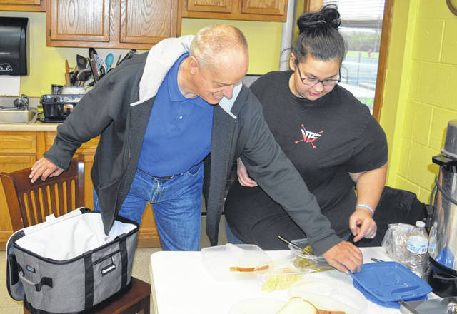 With the meals ready to go, Dennis Berwanger, left, and staff member Sarah Morgan, right, prepare to pack hot food in an insulated food carrier and then head out in a van to deliver meals to some local veterans.