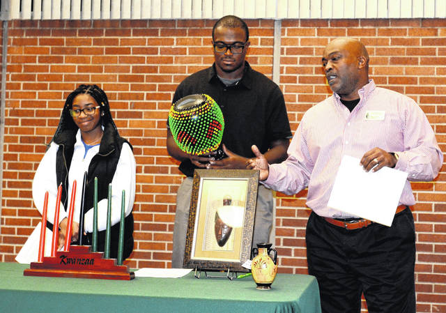 At the 2017 holiday tradition program, Chip Murdock , right, director of diversity and inclusion, explains some of Kwanzaa's finer points along with Black Student Initiative members Kelly Angevine and Sterling Clark, the latter of whom is holding a ceremonial skekere, a rhythm percussion instrument from Africa.