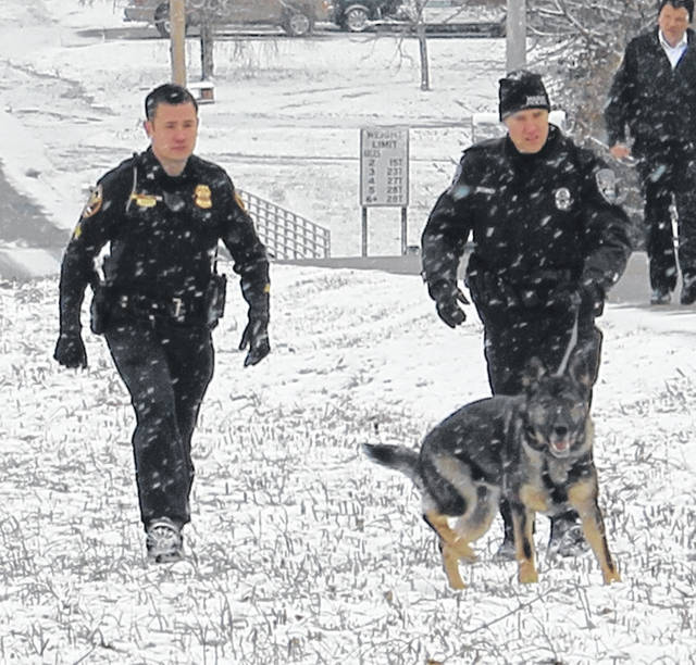 Blanchester Police Cpl. James Beckelhymer, Mason Police Officer Mike Sechrist and K-9 Banshee search for a gun that was reported to have been dumped in Blanchester.