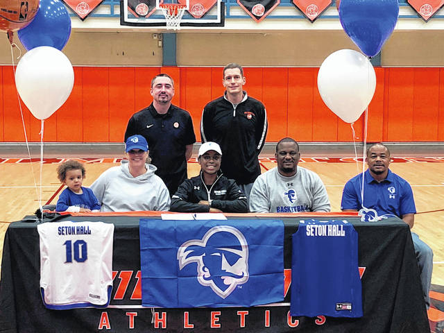 From left are: front, Max Isaac, Kim Isaac, Mya Jackson, Will Isaac and Jermaine Isaac; and, back, assistant coach Dustin James and head coach Zach Williams. Family, friends, teammates and coaches join in as Mya Jackson signs to attend and play basketball at Seton Hall University.