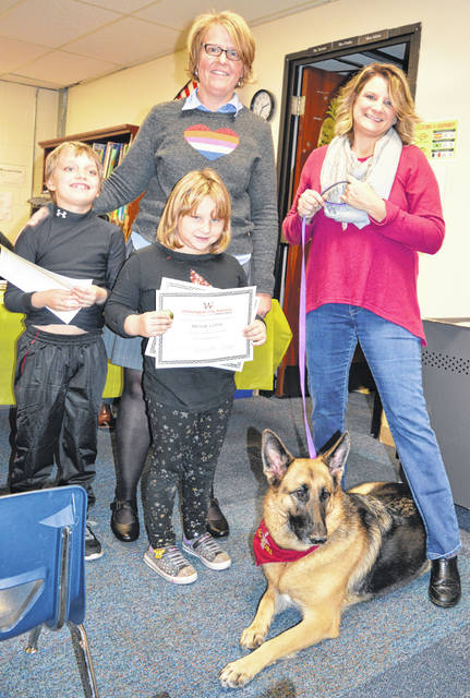 Kimi Hilderbrant, right, and her trained therapy dog Sydney, pictured, visit Holmes Elementary School in Wilmington about three times a week. They were recognized by Holmes Elementary Principal Karen Long, left. Young students who have helped Sydney and vice versa include, from left, Gavin Parley and Brook Copas. Sydney can help children open up and in other ways too, said Hilderbrant. Sydney can lift up her paw to signal bye-bye. Not present for the photo are Holmes Elementary students Elijha Faulkner, Bella Burwinkle, Camden McClanahan and Earl Faulkner.