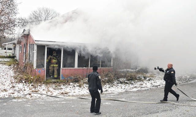 A Wilmington house at the 400 block of South Wall Street caught fire Thursday morning. In the photo, Wilmington police officer Patrick Black, right, assists with a fire hose and prepares to hand it off to a firefighter. More details on the blaze will be released when they become available.