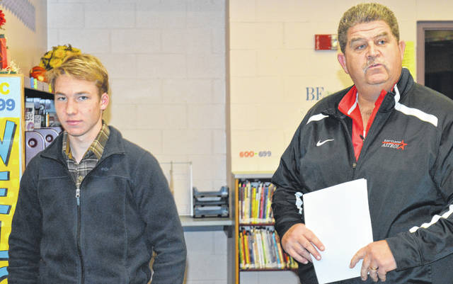 At the November school board meeting, East Clinton Athletic Director Jim Marsh, right, tells board members and the audience about East Clinton High School junior Aidan Henson, left. A cross-country runner, Henson was selected a Southern Buckeye Athletic and Academic Conference (SBAAC) boys cross country all-star; was named SBAAC National Division Runner of the Year; and placed eighth in Southwest District cross country, which qualified him for the Ohio High School Athletic Association regional. Marsh said Henson also is an SBAAC academic all-star with a 4.0 grade point average.