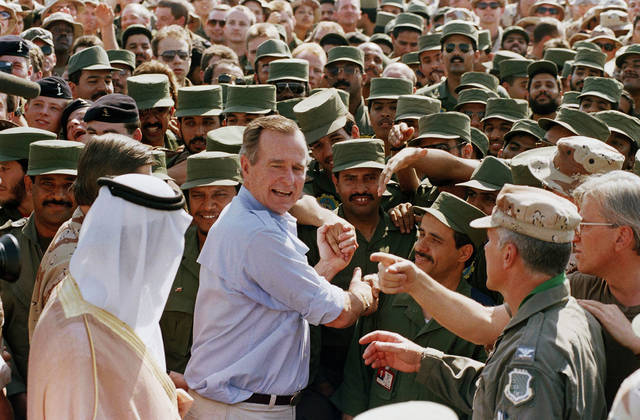 FILE - In this Nov. 22, 1990 file photo, President George H.W. Bush is greeted by Saudi troops and others as he arrives in Dhahran, Saudi Arabia, for a Thanksgiving visit. Bush died at the age of 94 on Friday, Nov. 30, 2018, about eight months after the death of his wife, Barbara Bush. (AP Photo/J. Scott Applewhite, File)
