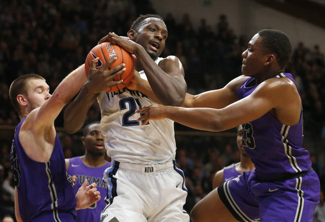 FILE - In this Saturday, Nov. 17, 2018, file photo, Villanova forward Dhamir Cosby-Roundtree (21) and Furman forward Matt Rafferty (32) and guard Jordan Lyons (23) fight for a rebound during the second half of an NCAA college basketball game, in Villanova, Pa. Furman coach Bob Richey wants his players to savor the program's first appearance in the AP Top 25 poll yet also remember how much work it took to get there. (AP Photo/Laurence Kesterson, File)