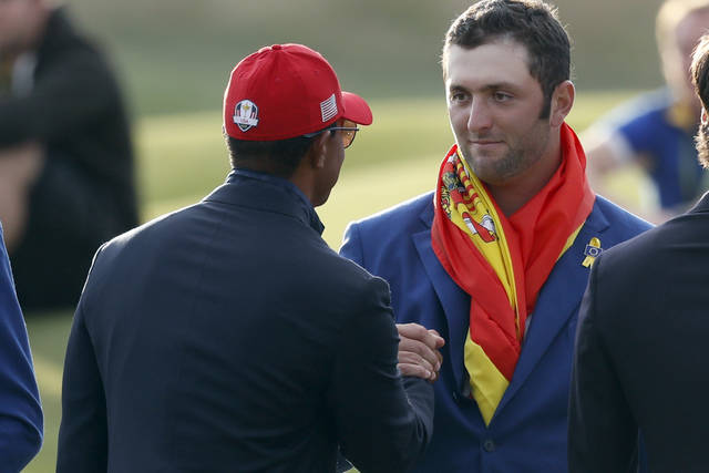FILE - In this Sept. 30, 2018, file photo, Europe's Jon Rahm, right, is congratulated by Tiger Woods during the trophy ceremony after the European team won the 2018 Ryder Cup golf tournament at Le Golf National in Saint Quentin-en-Yvelines, outside Paris, France. Rahm calls Woods his all-time hero and says this was the best moment of his career. (AP Photo/Alastair Grant, File)