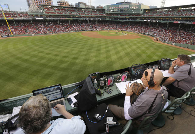 FILE - In this Aug. 3, 2014, file photo, ESPN television broadcasters prepare to cover a baseball game between the New York Yankees and the Boston Red Sox from the top of the Green Monster at Fenway Park, moments before the game, in Boston. ESPN plans to announce it will move up the starting time of the nationally televised game by one hour, with the first pitch planned for shortly after 7 p.m. EDT. The network intends to make the announcement on Monday, Dec. 10, 2018, at the winter meetings, a person familiar with the decision told The Associated Press. The person spoke on condition of anonymity Sunday because the announcement had not yet been made. (AP Photo/Steven Senne, File)