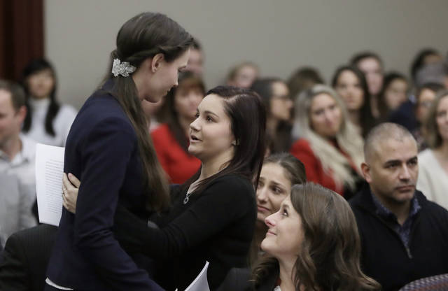 FILE - In this Jan. 24, 2018, file photo, former gymnast Rachael Denhollander, left, is hugged by Kaylee Lorincz after giving her victim impact statement during the seventh day of Larry Nassar's sentencing hearing in Lansing, Mich. More than 150 female athletes testified at Nassar's sentencing hearing in January 2018 for convictions on child-porn and sex-abuse charges. It marked a turning point in a crisis that has inflicted untold damage. (AP Photo/Carlos Osorio, File)