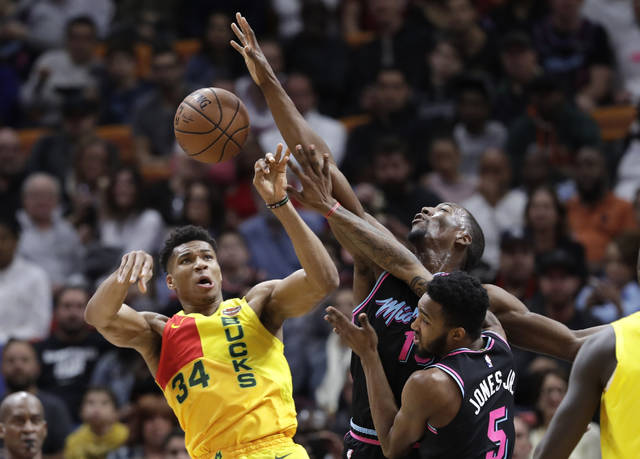 FILE - In this Dec. 22, 2018, file photo, Milwaukee Bucks forward Giannis Antetokounmpo (34) passes as Miami Heat center Bam Adebayo, center, and forward Derrick Jones Jr. (5) defend during the first half of an NBA basketball game in Miami. On Tuesday, Dec. 25, Antetokounmpo and the Bucks visit the New York Knicks as one of five games on the NBA's holiday schedule. (AP Photo/Lynne Sladky, File)