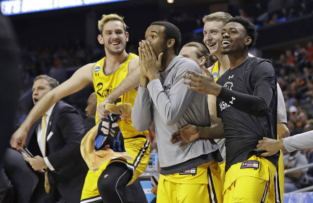 FILE - In this March 16, 2018, file photo, UMBC players celebrate a teammate's basket during the second half against Virginia i a first-round game in the NCAA men's college basketball tournament in Charlotte, N.C. (AP Photo/Gerry Broome, File)