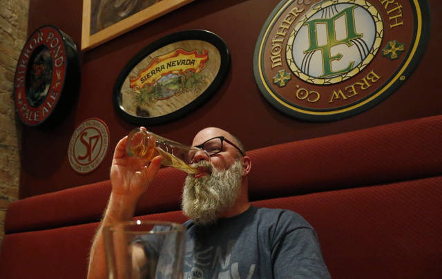 In this Dec. 20, 2018, photo, Rob Wheatley, 50, drinks a beer, at the Beer Hive Pub, in Salt Lake City. The United States' lowest DUI threshold takes effect this weekend in Utah. Lawmakers in the state approved the 0.05 percent blood-alcohol limit in 2017, and Gov. Gary Herbert signed it into law. The change goes into effect Saturday, Dec. 29, 2018. In a booth in the corner, recent Ohio transplant Wheatley said he drinks to try new craft beers, not to get drunk. He's skeptical that the law will be a serious deterrent for binge drinkers. (AP Photo/Rick Bowmer)
