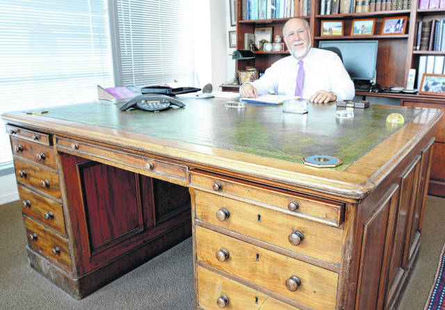 Daniel Buckley, a recently retired legal counselor and former adjunct faculty member in constitutional law for the College, sits at his father's desk.