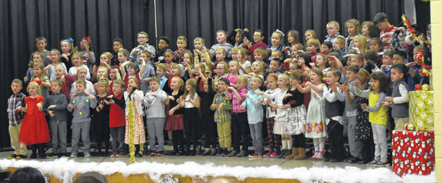 First-graders at Holmes Elementary School sing songs about a little Christmas tree that hopes Santa picks him as his tree during their Christmas show on Wednesday. Families of the students packed the auditorium while capturing memories with their cell phones during the performances conducted by music teacher Jamie Abel. For more photos, visit wnewsj.com.