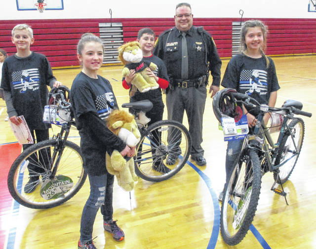 "Pictured with Clinton County Deputy Danny Wood are first-place winners Brendan Culberson and Kaylee McCollister with their new bikes, and second-place winners Sharon ""Shea"" McDonald and Nolan Phipps holding their DARE mascot, Daren the Lion."