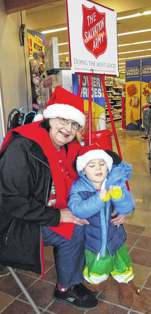 Mary Camp and great-grandson Xavier Phillips serve as bell ringers Saturday at the Salvation Army kettle inside the Wilmington Kroger.