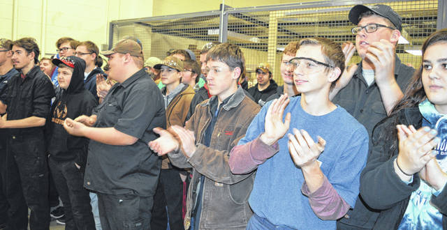 Students at Laurel Oaks Career Campus in Wilmington — including students of industrial diesel mechanics teacher Gary Bronson — applaud Mr. Bronson for securing the school and the industrial diesel mechanics program $100,000 in a nationwide competition.